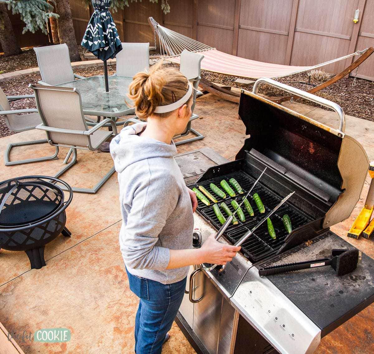 woman grilling zucchini in her backyard