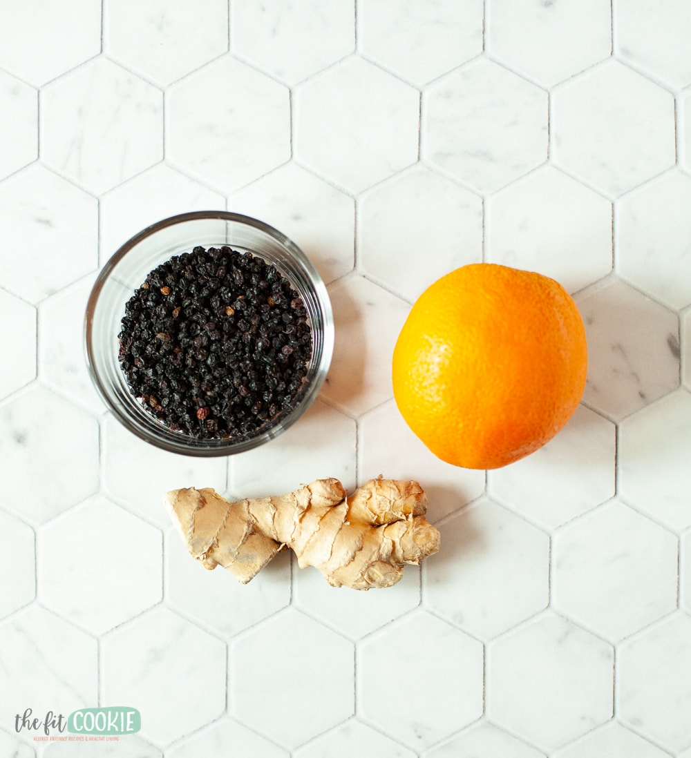 dried elderberries, orange, and ginger on a counter