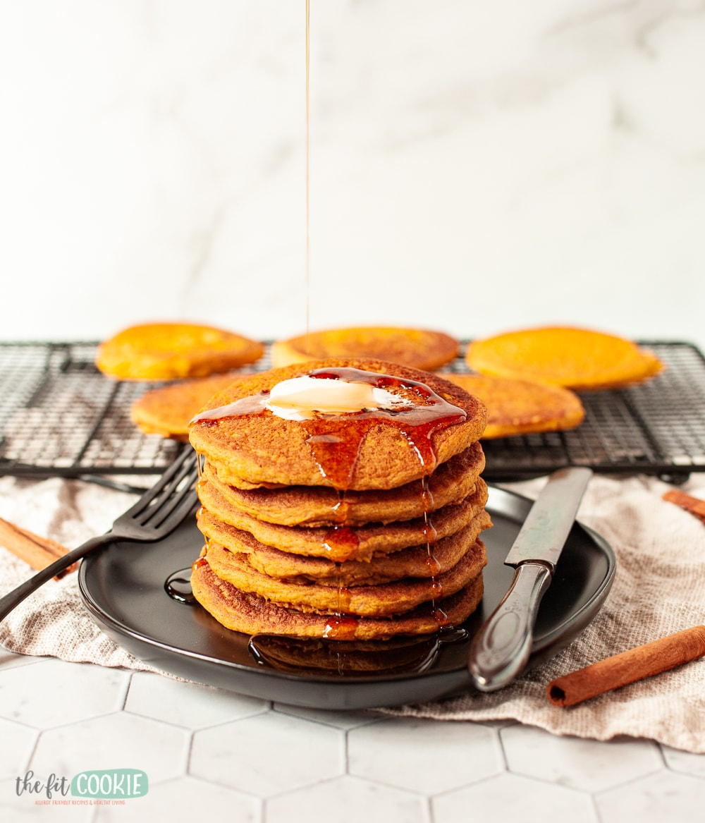 pumpkin spice pancakes on a black plate with maple syrup drizzled on top