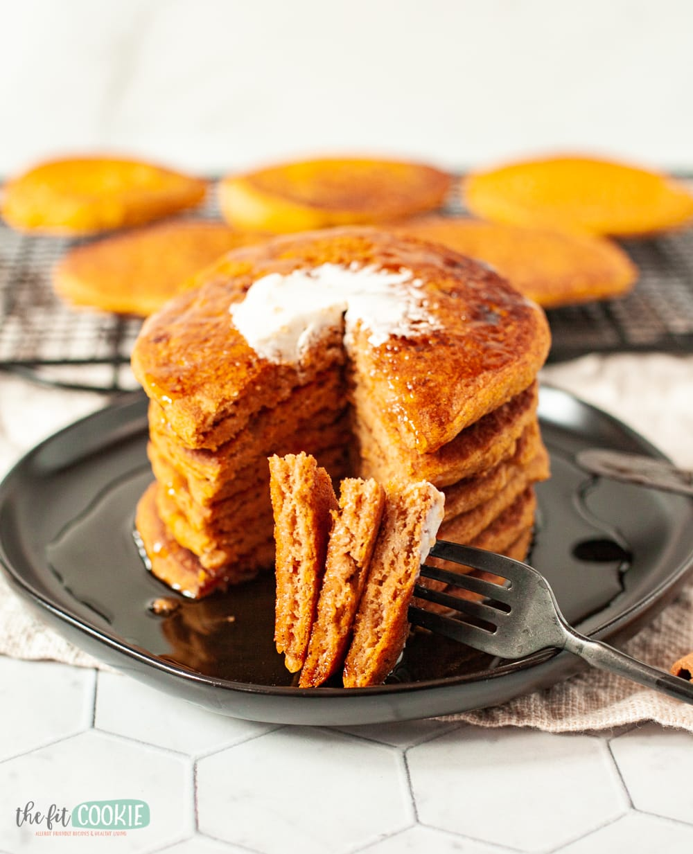 stack of gluten free pumpkin pancakes with bite of pancakes on a fork