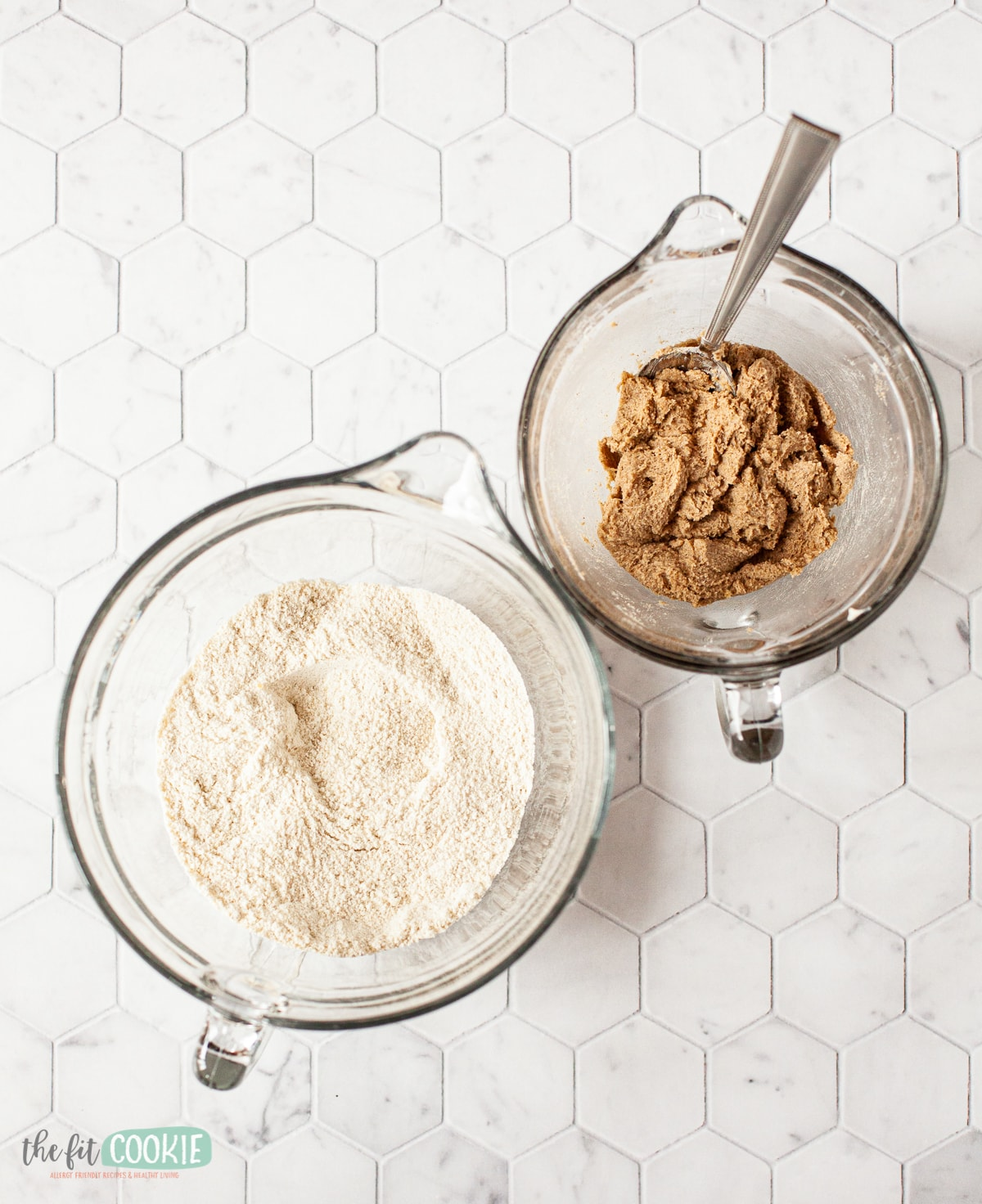 Bowl of flour next to bowl of cinnamon butter on tile counter