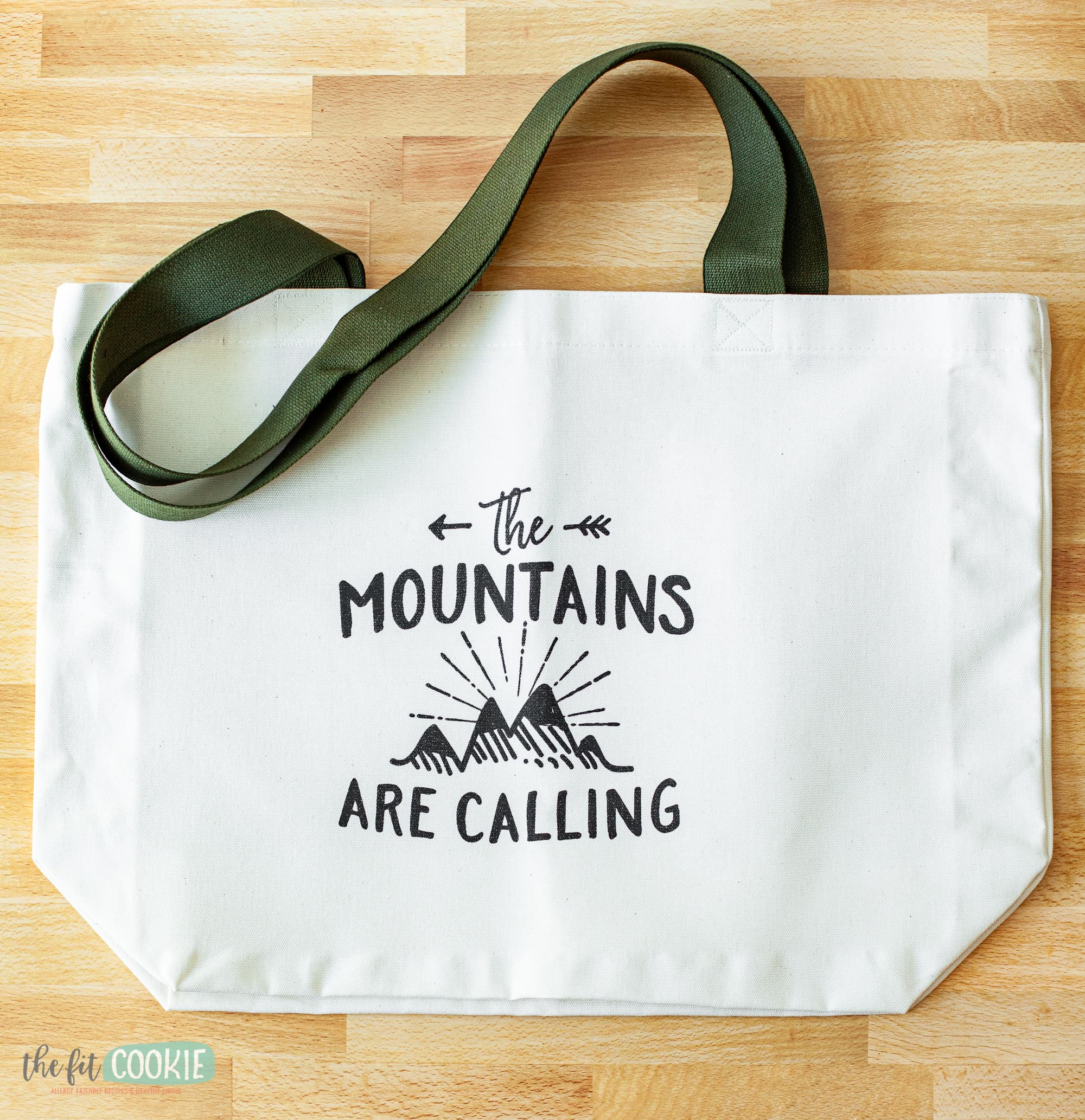 "white canvas tote with ""the mountains are calling"" in black ink"