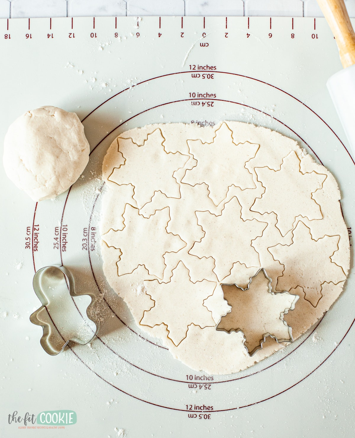 cookie dough on pastry mat with cookie cutters