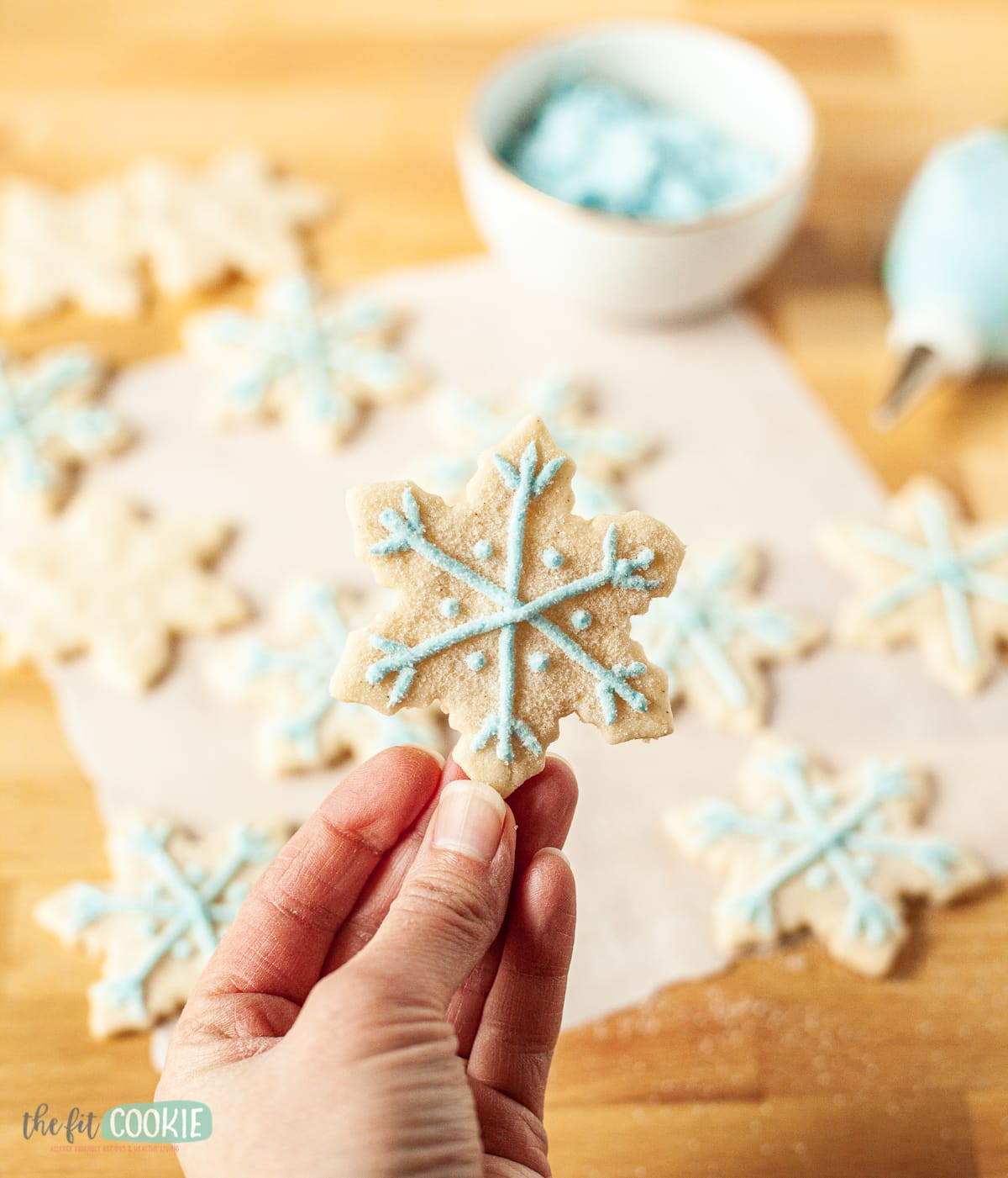 hand holding snowflake sugar cookie