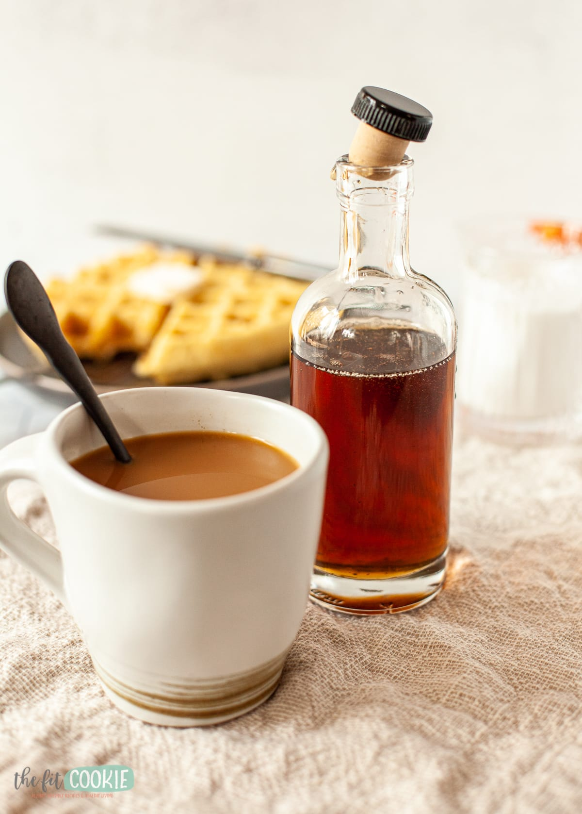 glass bottle of homemade coffee syrup and cup of coffee