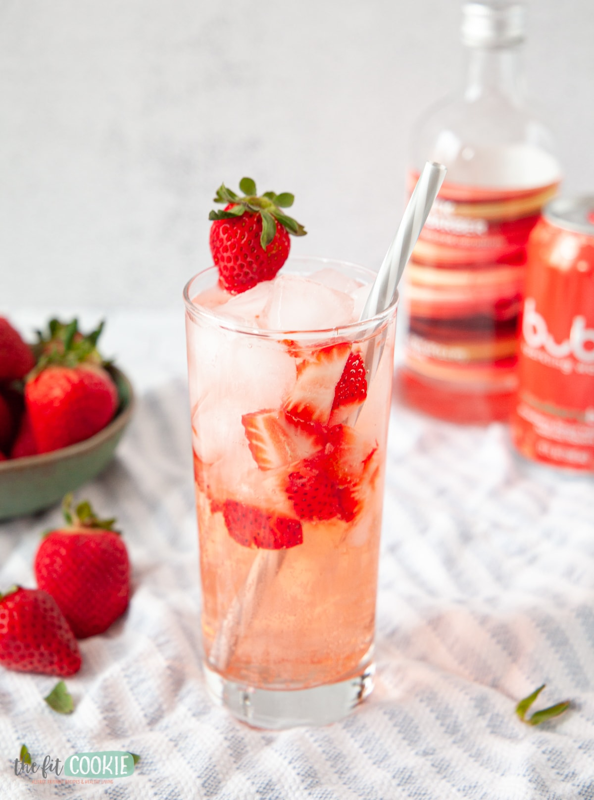 glass with strawberries, drink, and ice in it