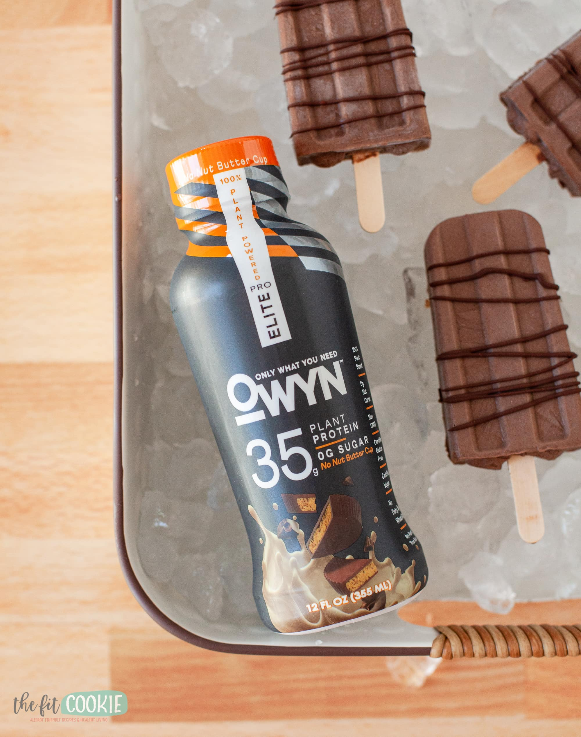 bottle of OWYN protein shake on ice with fudgesicles