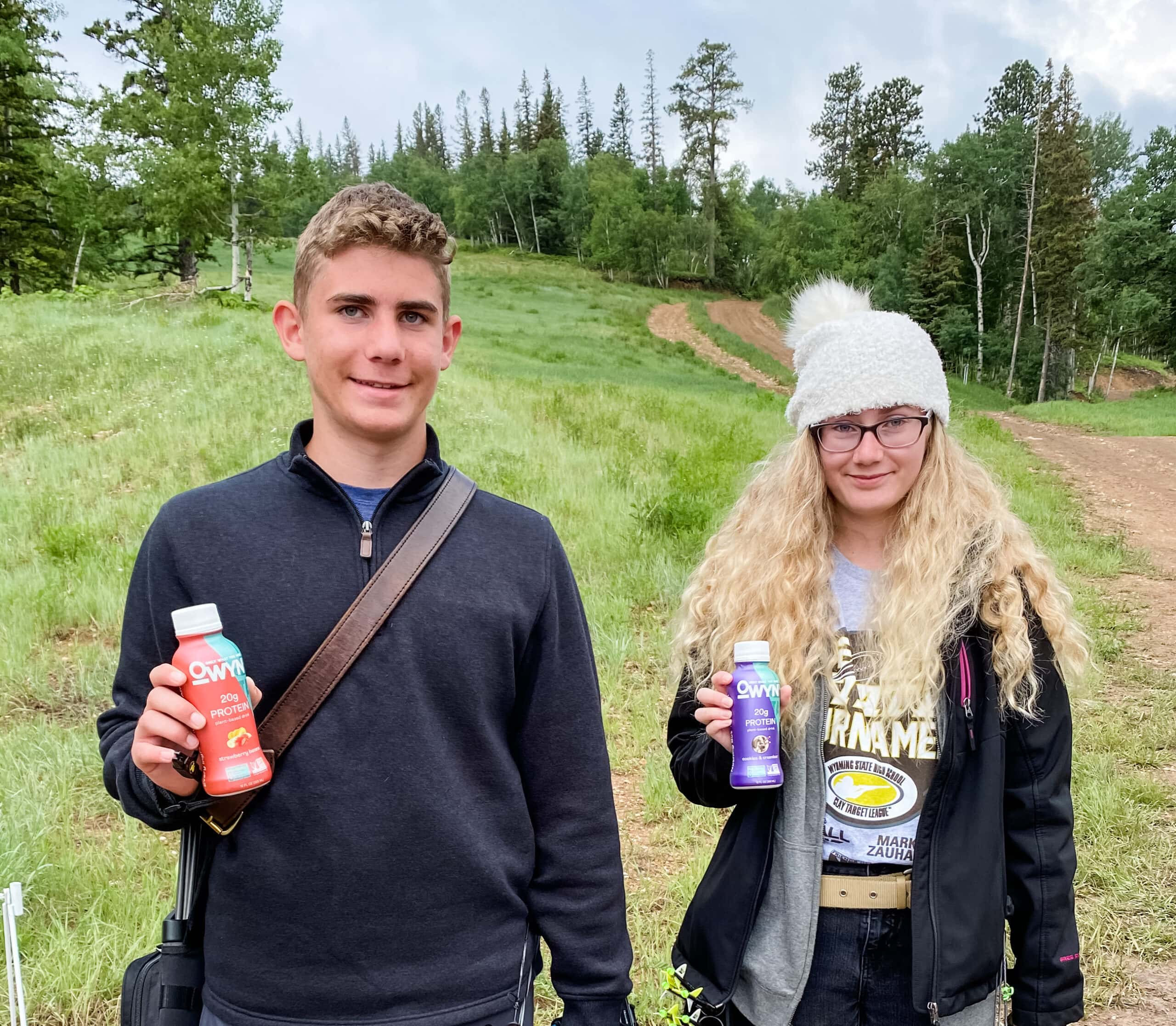 kids holding bottles of OWYN allergy friendly protein shakes