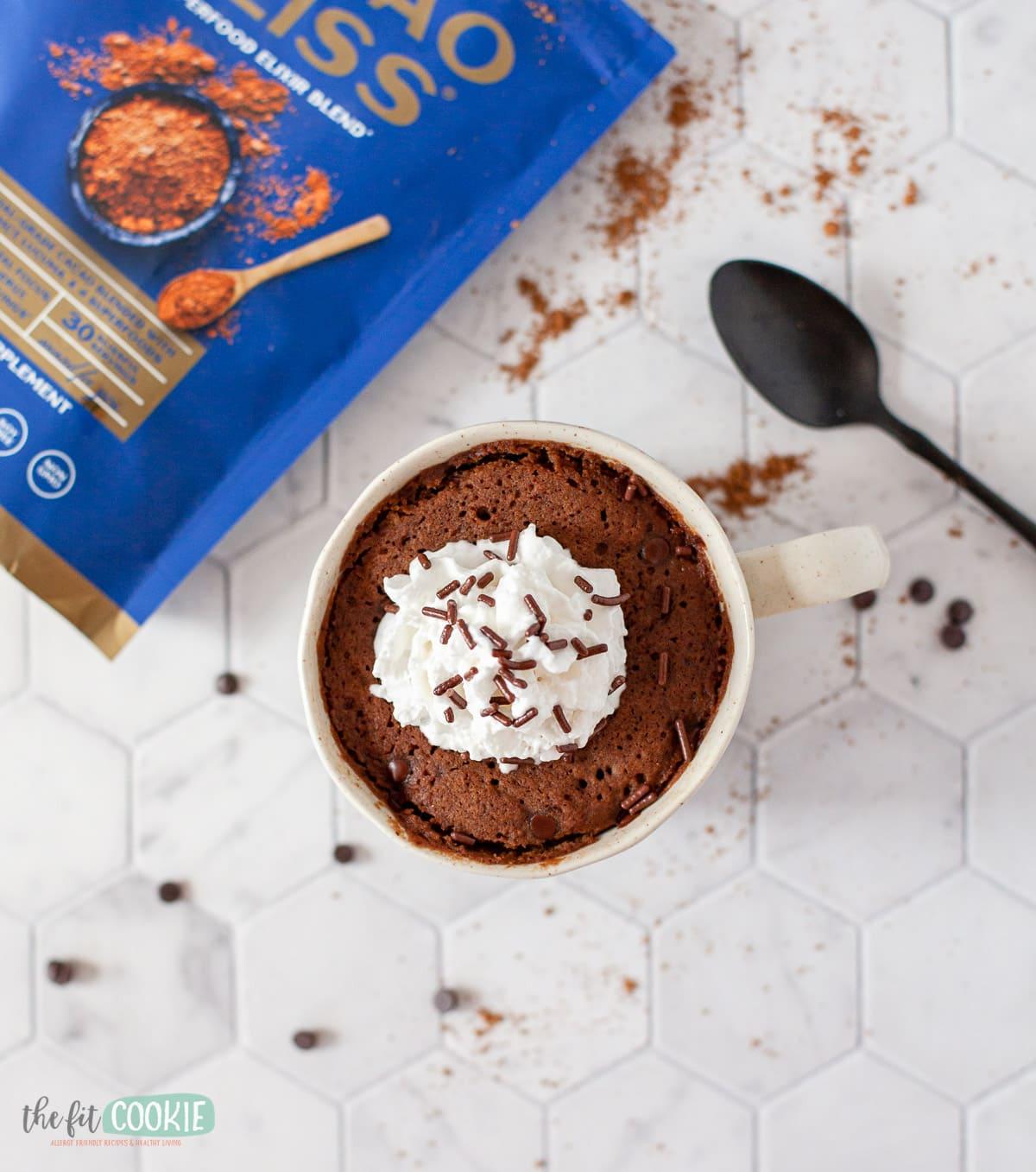 overhead photo of mug cake on a tile countertop