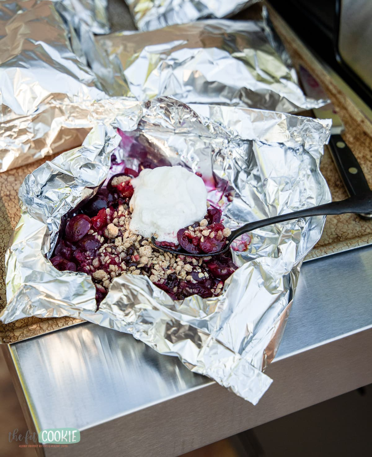 foil packet cherry crisp topped with dairy free whipped cream