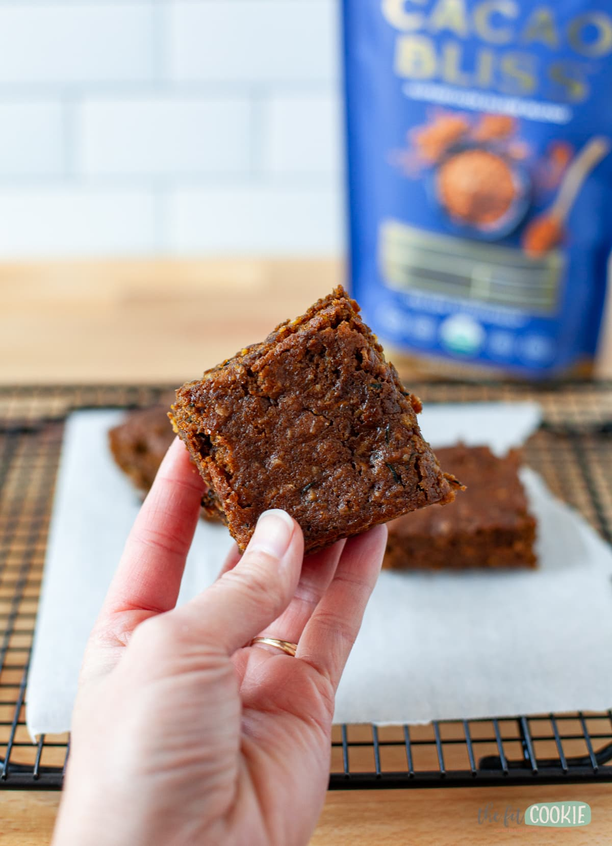 hand holding a chocolate zucchini bar in front of a cooling rack