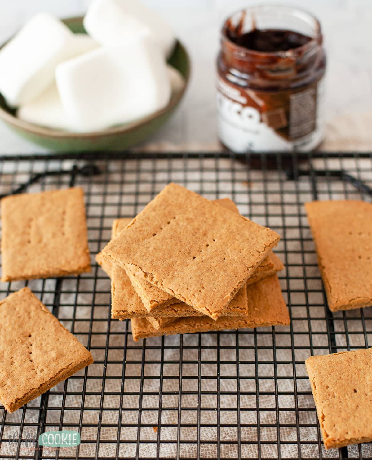 stack of dairy free graham crackers on a black cooling rack.