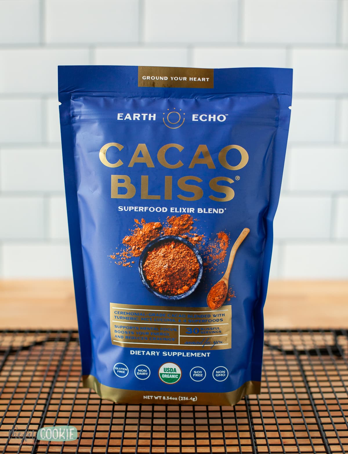 bag of cacao bliss powder on a black cooling rack