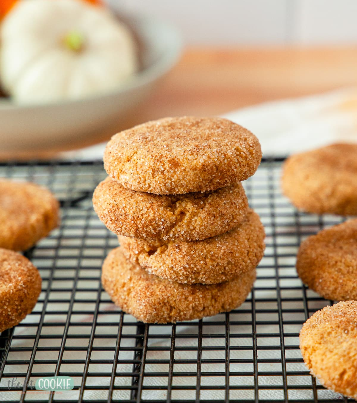 stack of pumpkin snickerdoodle cookies on a black cooling rack