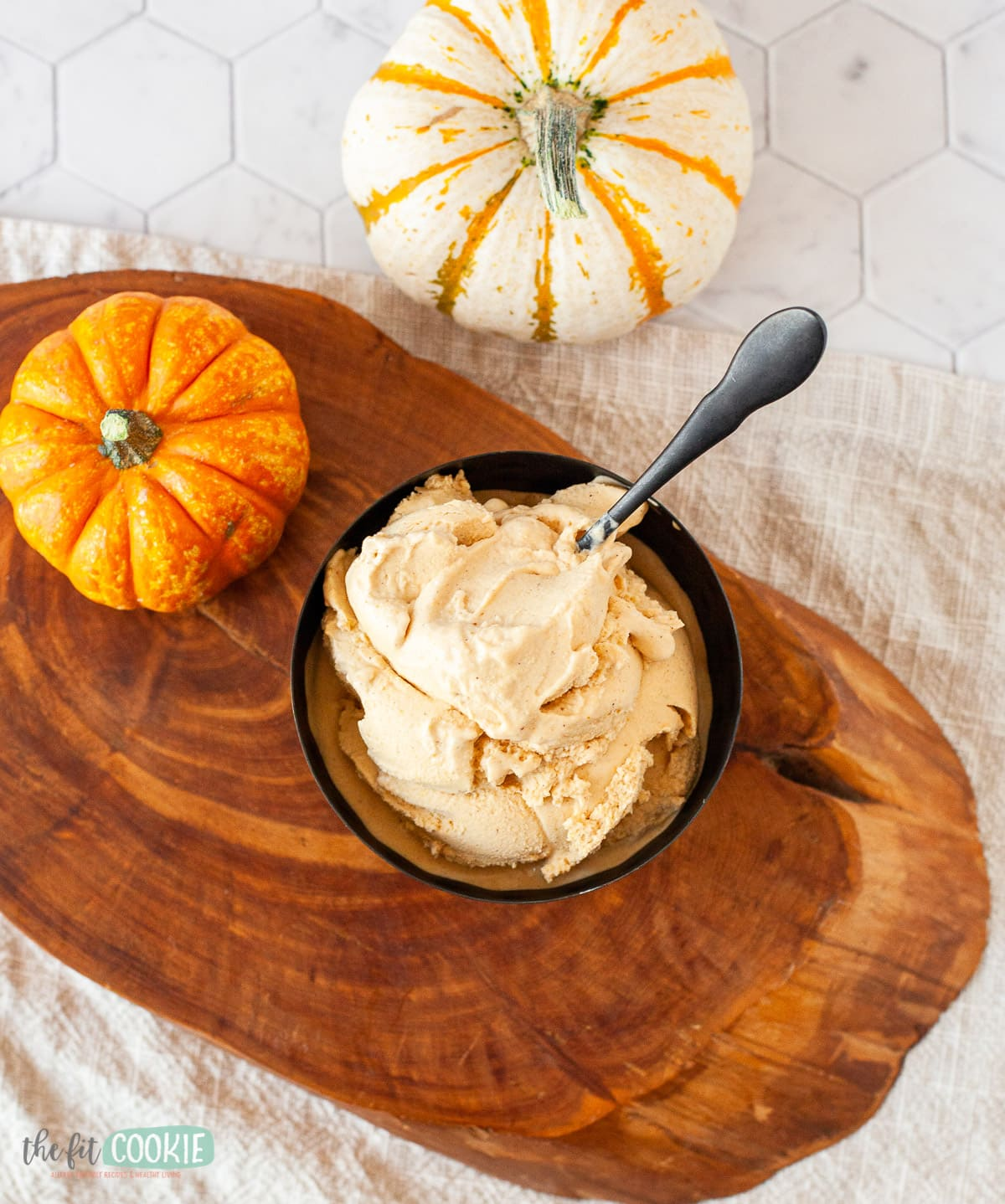 bowl of pumpkin spice ice cream on a wooden board